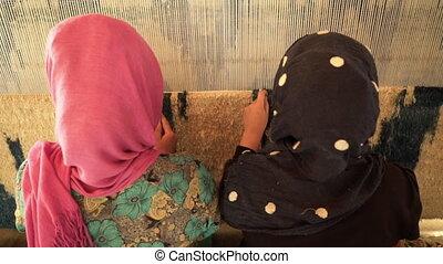 Weaving factory rugs - A close up shot of women weaving...