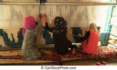 Weaving factory rugs - A medium moving shot of women weaving...