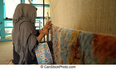 Weaving factory rugs - A medium panning shot of women...