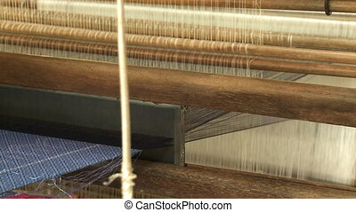 Weaving of silk using a traditional wooden loom - A steady...