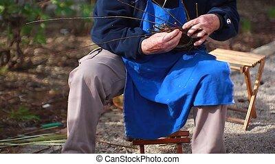 Weaving wicker basket - Old man weaving wicker basket in the...