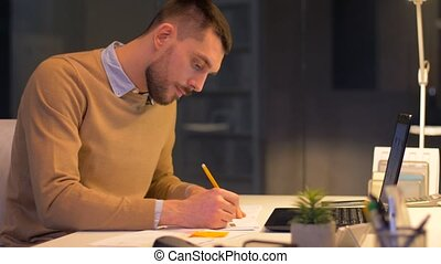 web designer with laptop working at night office