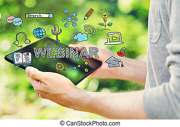 Webinar concepts with young man holding his tablet computer