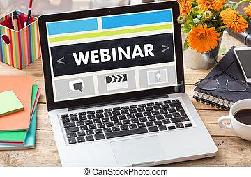 Webinar on a laptop screen on an office desk
