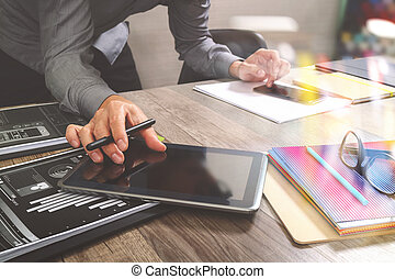 Website designer holding smart phone and working computer digital tablet on wood table