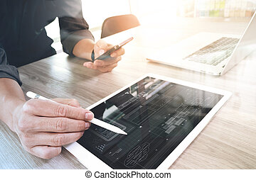 Website designer working digital tablet and computer laptop and digital design diagram on wooden desk as concept