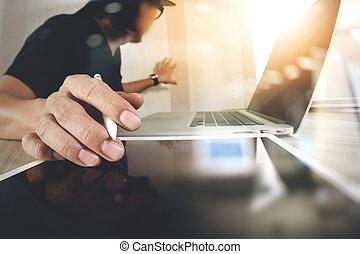Website designer working digital tablet and computer laptop on wooden desk as concept