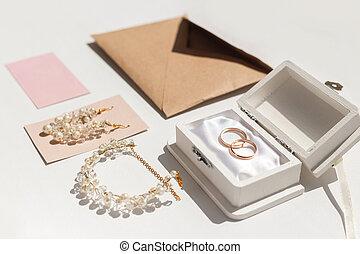 Wedding accessories background. Golden wedding rings and feminine accessories.