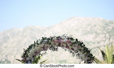 Wedding arch of roses. Wedding ceremony at the church in Prcanj,