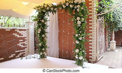 Wedding arch with white flowers against a brick wall.