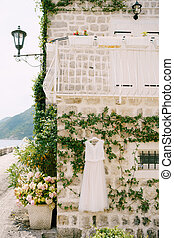 Wedding attire of the bride against the backdrop of a stone wall of a house with a balcony on the second floor and jasmine winding along the wall, in an old villa in Perast, Montenegro.