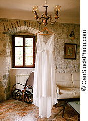 Wedding attire of the bride on a wooden hanger on a chandelier in a room with a sofa and a rocking chair.