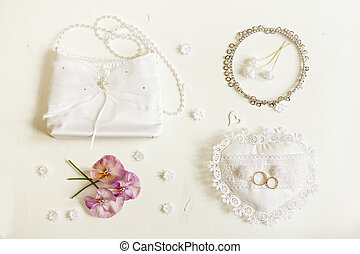 Wedding background. Bride accessories: rings, handbag, boutonniere, necklace.