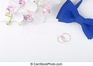 wedding background with golden rings on white wooden table