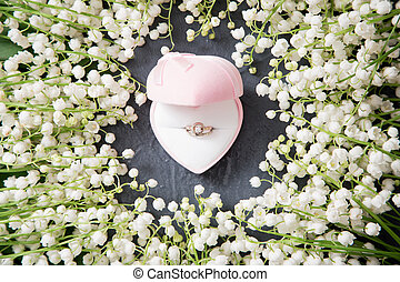 Wedding background with rings and lilies of the valley.