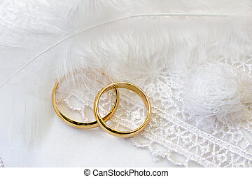 Wedding background with rings and feather.