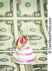 Wedding bands on money and a cake
