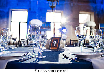 Wedding. Banquet. The chairs and round table for guests, served with cutlery and crockery and covered with a blue tablecloth.