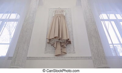 Wedding beige dress hanging on wall inside space room in big house