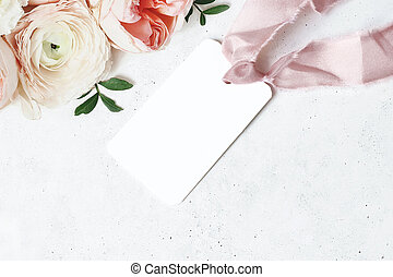 Wedding, birthday stationery mock-up scene. Blank gift tag, label with pink silk ribbon. Decorative floral corner. Green leaves, pink English rose and ranunculus flowers. Concrete table background.