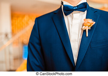 Wedding bouquet a boutonniere on a suit of the groom.