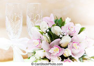 Two glasses of champagne and a beautiful tender festive wedding bouquet of flowers, buttercups and white lilac on a white painted wooden board.