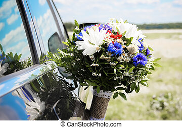 Wedding bouquet at the door of a black car