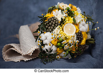 Wedding bouquet from cotton, lemon, chamomile on a green grass