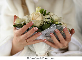 Wedding bouquet - Hands of the bride with a ring and bouquet