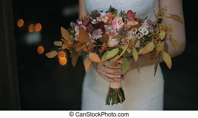 Wedding bouquet in bride hands indoors. Burning candles on a background. Bride is holding beautiful wedding bouquet of different flowers.