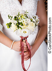 Wedding bouquet in bride's hands with a brown tape