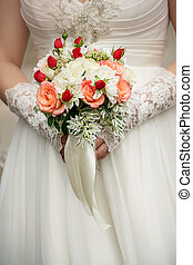 Wedding bouquet in bride's hands with a white tape