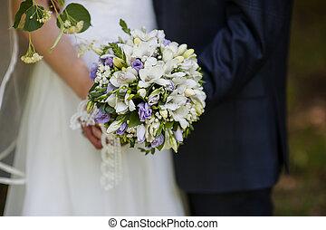 Wedding bouquet in hands of the bride and groom