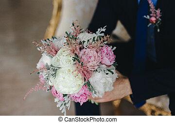 wedding bouquet in hands of the groom