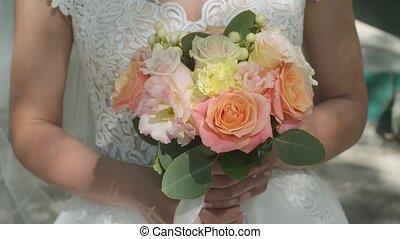 Wedding bouquet in the hands of the bride. Sunny day, colorful roses, close-up.