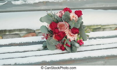 wedding bouquet lying on a snowy bench in the winter