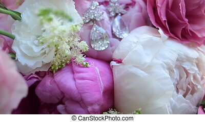 wedding bouquet of peonies and inside are earrings of...