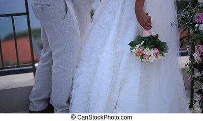 Wedding bouquet of pink roses in bride's hands.