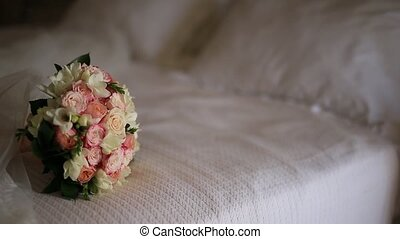 Wedding bouquet of pink roses on the bed