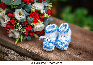 Wedding bouquet of roses and baby booties on wooden background