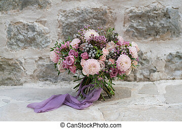 wedding bouquet of various flowers on a stone wall background