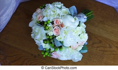 Wedding bouquet of white roses on a wooden table. top view.
