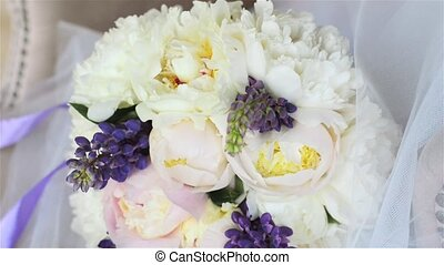 Wedding bouquet on a white armchair in a luxury photo studio. Bouquet of peonies and lupines with a purple ribbon.