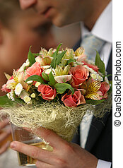 Wedding bouquet in a hand of the groom