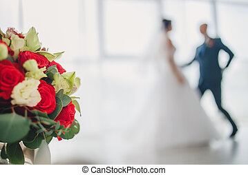 Wedding bouquet roses on a background of the bride and groom in dance