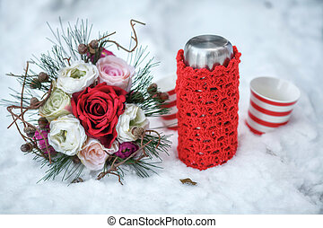 Wedding bouquet, thermos and mug in snow