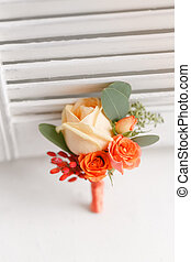 wedding boutonniere of orange roses to the man to the groom. white background.