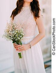 Wedding bridal bouquet of Gypsophila in the hands of the bride.