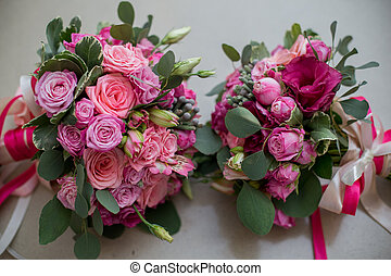 wedding bridal bouquet with pink flowers lying on the bed