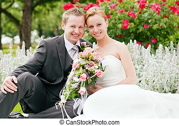 Newlywed couple - bride and groom - in a park after their wedding